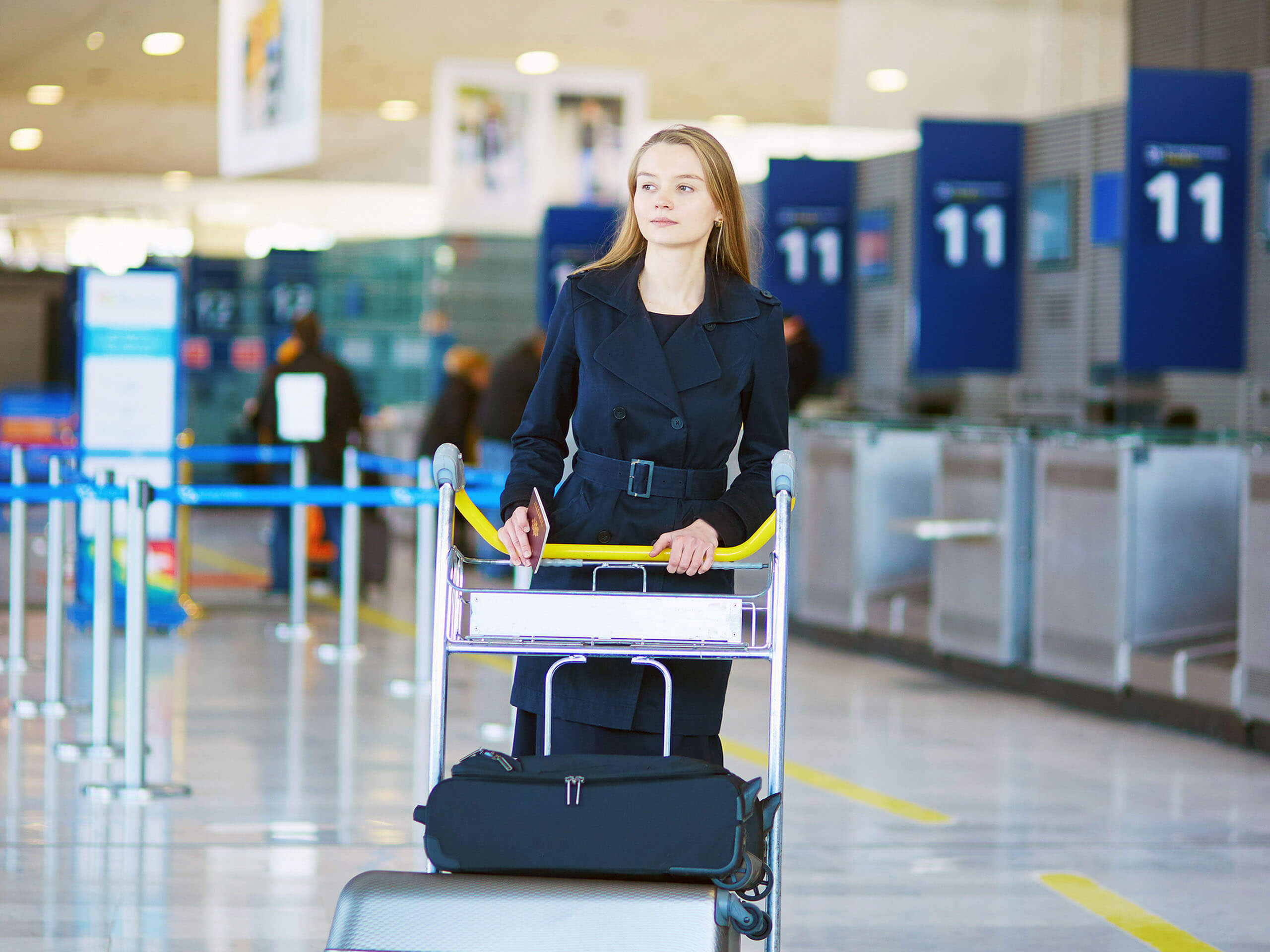 Woman with baggage trolley at the airport